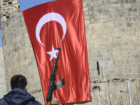 A Turkish policemen holds his AK-47 in front of a huge Turkish flag as he walks in front of Diyarbakir castle on February 3, 2016. Vowing to flush out the Kurdistan Worker's Party (PKK) from Turkey's urban centres, the authorities have in recent weeks enforced curfews in three locations in …