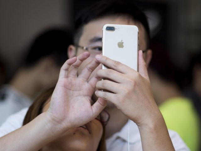 TOPSHOT - A Chinese couple tests the new iPhone 7 during the opening sale launch at an Apple store in Shanghai on September 16, 2016.