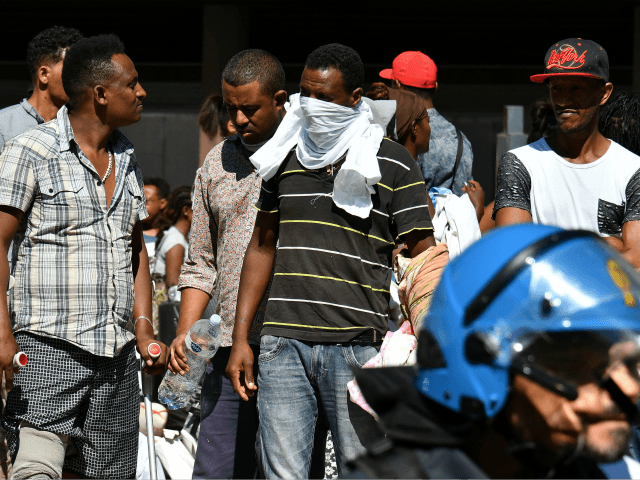 Refugees and asylum seekers wait after being displaced from a palace in the center of Rome on August 23, 2017. The UN's refugee agency (UNHCR) voiced 'grave concern' over the eviction of 800 people from a Rome building squatted mainly by asylum seekers and refugees from Eritrea and Ethiopia. The …