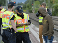German policemen check a 16 year-old boy from Eritrea after finding him under a train trailer at the train station in the southern German city of Raubling on August 24, 2017 during a search for illegal migrants on the German-Austrian border. / AFP PHOTO / Guenter SCHIFFMANN (Photo credit should …