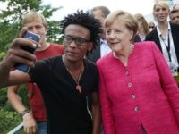 BERLIN, GERMANY - AUGUST 27: German Chancellor Angela Merkel pauses for a selfie with a young man who came alone as a refugee from Eritrea to Germany among visitors during the annual open-house day at the Chancellery on August 27, 2017 in Berlin, Germany. Germany will hold federal elections on …