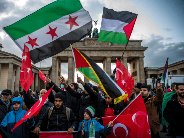 Demonstrators wave Palestinian, Turkish and Syrian flags in front of the Brandenburg Gate, next to the US embassy in Berlin on December 8, 2017, following US President Donald Trump's decision to recognise Jerusalem as the capital of the Israeli state. / AFP PHOTO / John MACDOUGALL (Photo credit should read …