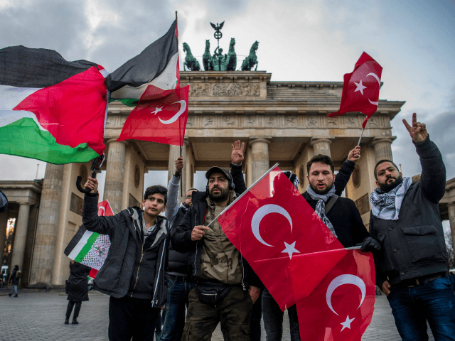 Demonstrators wave Palestinian and Turkish flags in front of the Brandenburg Gate, next to the US embassy in Berlin on December 8, 2017, following US President Donald Trump's decision to recognise Jerusalem as the capital of the Israeli state. / AFP PHOTO / John MACDOUGALL (Photo credit should read JOHN …