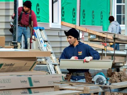 Construction workers install exterior beaded vinyl siding to a new home in Ashburn, Virginia on January 2, 2015.