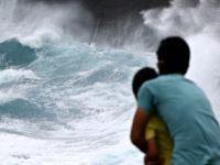 A man from Japan and his son watch as waves crash off sea cliffs along the southeast shore of Oahu as Hurricane Lane approaches, Friday, Aug. 24, 2018 near Honolulu.