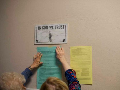 Election officials affix voting notices to the wall, below a plaque that states 'IN GOD WE TRUST,' at the Hazleton City Hall polling station before voters arrive for the 2018 Pennsylvania Primary Election on May 15, 2018 in Hazleton, Pennsylvania. In the second major May primary day nationwide, four states …