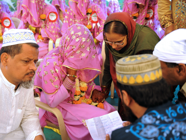 An Indian Muslim bride (C) answers questions by religious leaders during the 'Nikah Kabool Hai' or 'Do You Agree for the Marriage' in the presence of a bride's relative during a mass wedding ceremony in Ahmedabad on October 24, 2010. Some 65 Muslim couples participated in a mass wedding ceremony …