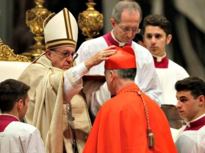 New Cardinal Blase Cupich receives the red three-cornered biretta hat during a consistory inside the St. Peter's Basilica at the Vatican on Saturday.