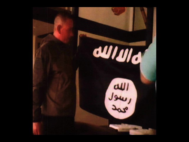 In this image taken from FBI video and provided by the U.S. Attorney's Office in Hawaii on Thursday, July 13, 2017, Army Sgt. 1st Class Ikaika Kang holds an Islamic State group flag after allegedly pledging allegiance to the group at a house in Honolulu on July 8. (FBI/U.S Attorney's …