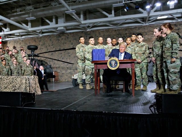 President Donald Trump signs a $716 billion defense policy bill named for Sen. John McCain Monday, Aug. 13, 2018, in Fort Drum, N.Y.