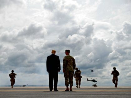 President Donald Trump talks with Maj. Gen. Walter Piatt as they watch an air assault exercise at Wheeler-Sack Army Air Field in Fort Drum, N.Y., Monday, Aug. 13, 2018,
