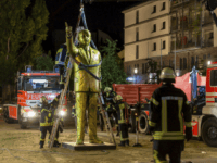 In this Aug. 28, 2018 photo a crane of the firebrigade lifts a statue of Turkish President Recep Tayyip Erdogan in Wiesbaden, western Germany. The statue was part of a controversial art project of the Wiesbaden Biennale. (Sebastian Stenzel/Wiesbaden112.de/dpa via AP)