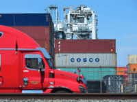 A container delivery truck passes containers stacked at the Port of Long Beach in Long Beach, California on July 6, 2018, including one from COSCO, the Chinese state-owned shipping and logistics company. - The twin ports of Long Beach and Los Angeles in Southern California are fearing a decline in …
