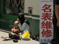 A Muslim ethnic Uighur woman begs with her baby on a street in Urumqi, capital of China's Xinjiang region on July 2, 2010 ahead of the first anniversary of bloody violence that erupted between the region's Uighurs and members of China's majority Han ethnicity. The government says nearly 200 people …