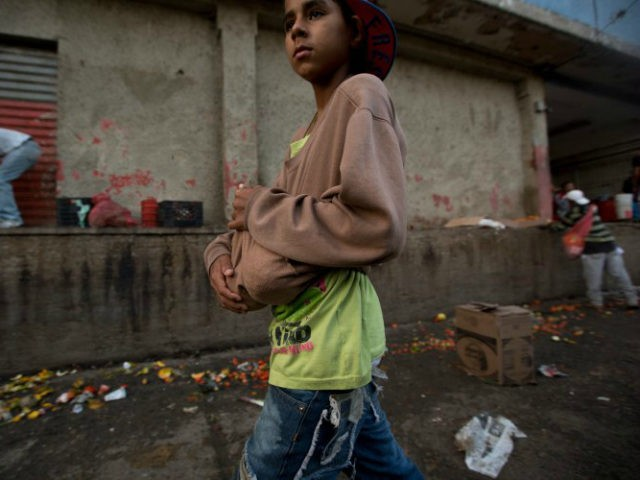 A boy carries two pineapples he found in the trash area of the Coche public market in Caracas, Venezuela. (Fernando Llano/AP)