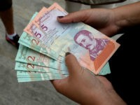 A woman holds new Bolivar-notes in downtown Caracas on August 21, 2018. - Caracas is issuing new banknotes after lopping five zeroes off the crippled bolivar, casting a pall of uncertainty over businesses and consumers across the country. (Photo by Federico PARRA / AFP) (Photo credit should read FEDERICO PARRA/AFP/Getty …