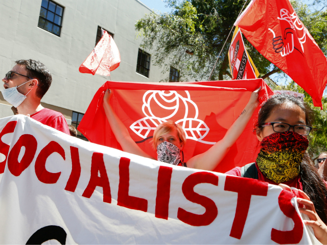 Democratic Socialists of America counter protesters hold signs and flags as they march, protesting an alt-right rally on August 5, 2018 in downtown Berkeley, California.. (Photo by Amy Osborne / AFP) (Photo credit should read AMY OSBORNE/AFP/Getty Images)