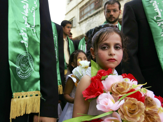 GAZA CITY, GAZA STRIP - AUGUST 05: A young relative stands with a groom during a mass wedding organized by the Palestinian party Hamas August 5, 2005 in Gaza City, the Gaza Strip. The brides have a separate ceremony in private. During the two-day celebration, 111 couples will be married. …