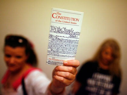 WASHINGTON - JULY 25: Elementary school teacher Lisa Petry of Virginia Beach, Virginia, holds up a copy of the U.S. Constitution while waiting in line to attend the House Judiciary Committee's hearing on the 'Executive Power and Its Constitutional Limitations' at the Rayburn House Office Building on Capitol Hill July …
