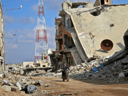 A Syrian man rides his motorcycle past damaged buildings in the southern city of Daraa, on March 16, 2017. Daraa province, the cradle of the 2011 uprising against President Bashar al-Assad's regime, is mostly held by the rebels but pro-government forces and Islamic State are also present. / AFP PHOTO …