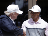 Donald Trump, left, shakes hands with Tiger Woods during a ribbon cutting for the new Tiger Woods Villa at the Trump National Doral golf course, Wednesday, March 5, 2014 in Doral, Fla. (AP Photo/Wilfredo Lee)