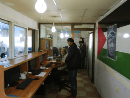 Palestinian men work at a passport control station held by the Palestinian Authority at the northern entrance of the Gaza Strip just after the Israeli-controlled Erez crossing, on November 1, 2017 in Beit Hanun. An AFP journalist saw Hamas installations at a separate checkpoint with Israel being dismantled. Under the …