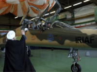 In this photo released by the official website of the office of the Iranian Presidency, President Hassan Rouhani, left, waves to the pilots of a fighter jet, before an inauguration ceremony of the aircraft, Iran, Tuesday, Aug. 21, 2018. Iran on Tuesday displayed a new twin-seat fighter jet it says …