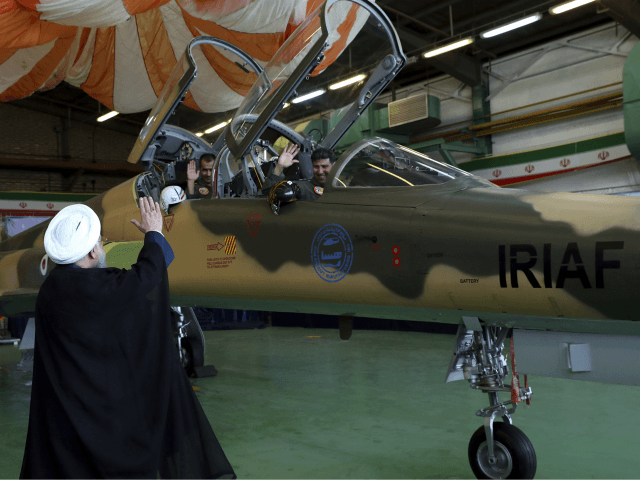 In this photo released by the official website of the office of the Iranian Presidency, President Hassan Rouhani, left, waves to the pilots of a fighter jet, before an inauguration ceremony of the aircraft, Iran, Tuesday, Aug. 21, 2018. Iran on Tuesday displayed a new twin-seat fighter jet it says is all Iranian-made and which allegedly has advanced avionics and fire control systems. (Iranian Presidency Office via AP)