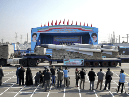 In front of the portraits of supreme leader Ayatollah Ali Khamenei, right, and the late revolutionary founder Ayatollah Khomeini, left, a missile is displayed by Iran's army during a parade marking National Army Day at the mausoleum of Khomeini, just outside Tehran, Iran, Wednesday, April 18, 2018. (AP Photo/Ebrahim Noroozi)