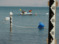 Israel children play on August 24, 2008 on a boat near water measurement scales at the Sea of Galilee in northern Israel, which has seen a big decrease of its water level. The Jordan River supplies 95% of the water in the Sea of Galilee sweet lake. After four consecutive …
