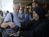 United Kingdom's Labour party leader Jeremy Corbyn is offered candy by Syrian refugee Sohela Sobeihi, 52 while talking to refugees at the main market road, during his visit to the Zaatari Syrian Refugee Camp, in Mafraq, Jordan, Friday, June 22, 2018. (AP Photo/Nasser Nasser)