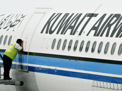 A ground crewmember takes a peek inside the cabin of a Kuwait Airways Airbus A340 at the Kuala Lumpur International Airport in Sepang, 01 November 2006. Kuwait Airways began twice-weekly flight operations from Kuwait to Kuala Lumpur with its maiden flight 01 November. AFP PHOTO/TENGKU BAHAR (Photo credit should read …