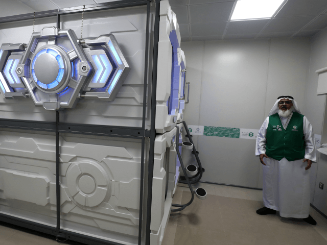 Mansour al-Amer, head of Saudi charity the Haji and Mutamer Gift Charitable Association, stands next to sleep pods in Mecca on August 16, 2018. - The free nap pods are part of new measures Saudi Arabia is rolling out this year in a bid to modernise the centuries-old practice of …
