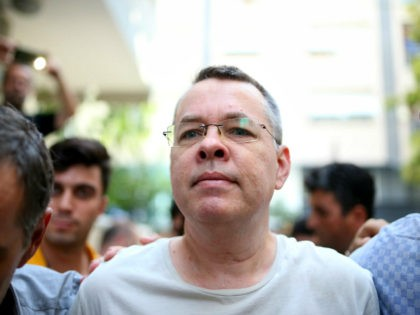 Pastor Andrew Craig Brunson (R), escorted by Turkish plain clothes police officers as he arrives at his house on July 25, 2018 in Izmir. - A Turkish court on July 25, 2018 ruled to place under house arrest an American pastor who has been imprisoned for almost two years on …