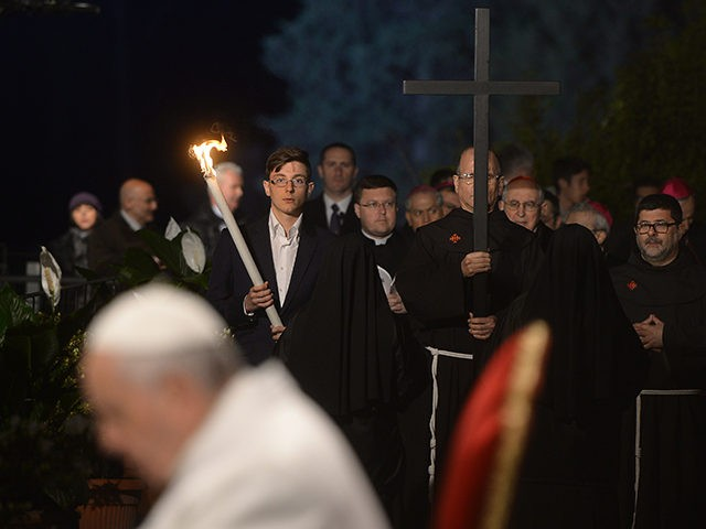 Penitents carry the cross next to Pope Francis during the Way of the Cross torchlight procession at the Colosseum on Good Friday on April 3, 2015 in Rome. Christians around the world are marking the Holy Week, commemorating the crucifixion of Jesus Christ, leading up to his resurrection on Easter. …