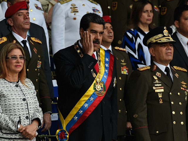 Venezuelan President Nicolas Maduro (C) gestures between his wife Cilia Flores (L) and Defence Minister General Vladimir Padrino during a ceremony to celebrate the 81st anniversary of the National Guard in Caracas on August 4, 2018 day in which Venezuela's controversial Constituent Assembly marks its first anniversary. - The Constituent …