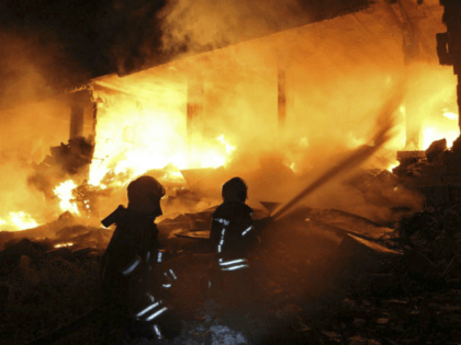 This photo provided by the Syrian Civil Defense White Helmets, which has been authenticated based on its contents and other AP reporting, shows Syrian White Helmet civil defense workers extinguishing a fire at the scene of an explosion that hit a five-story building, in the village of Sarmada, near the …