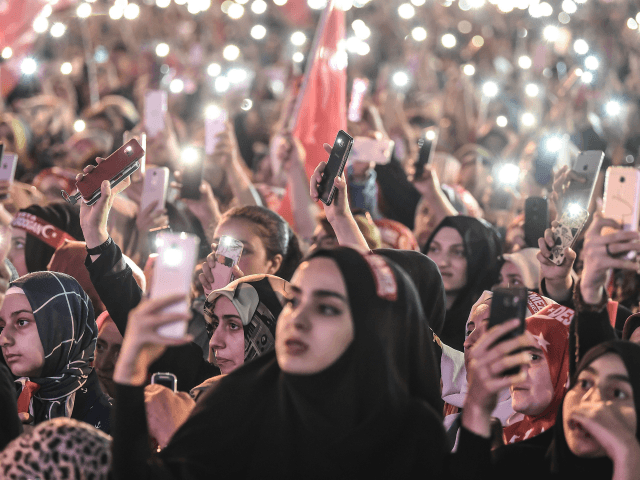 People lit lights of their mobile phones as they read the names of people killed during the July 15, 2016 coup attempt, while standing near the 'July 15 Martyrs Bridge' (Bosphorus Bridge) in Istanbul on July 15, 2018. - Turkey on commemorated the second anniversary of a bloody coup attempt …