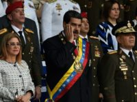 Venezuelan President Nicolas Maduro (C) gestures between his wife Cilia Flores (L) and Defence Minister General Vladimir Padrino during a ceremony to honor the National Guard in Caracas