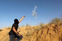 A masked Palestinian launches a balloon loaded with flammable materials to be flown toward Israel, at the Israel-Gaza border, in Rafah in the southern Gaza Strip