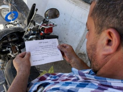 A man holds a leaflet stamped with the government forces' seal and dropped by helicopters over the northwestern Syrian town of Binnish warning of an impending assault on Idlib province and urging surrender