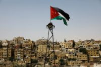 A Jordanian flag flutters above the Jordanian capital Amman on June 8, 2018