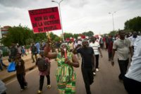 "A demonstrator holds up a placard reading ""no to theft of the victory of the people"" during a protest against incumbent Malian president Ibrahim Boubacar Keita in Bamako"