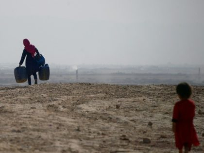 A girl carries containers to collect water on the outskirts of Mazar-i-Sharif in northern Afghanistan, where a lack of snow and rain in recent months has badly hit the harvest, sparking warnings of severe food shortages