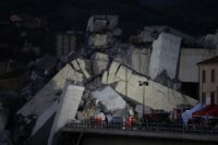 Rescuers scour through the wreckage overnight after a vast span of the Morandi bridge collapsed during a heavy rainstorm in Genoa