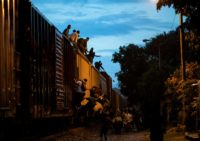 "Undocumented migrants climb on a train known as ""La Bestia"" (The Beast), in the town of Las Patronas in Mexico's Veracruz state hoping to reach the US"