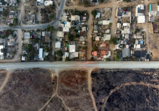 Aerial view of houses and structures sitting right next to the Mexico-US border fence at El Nido de las Aguilas in eastern Tijuana, Baja California State, Mexico, taken on July 26, 2018