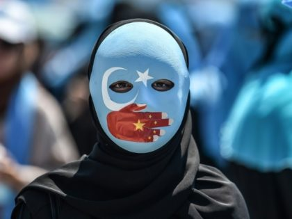 A demonstrator wears a mask painted with the colors of the flag of East Turkestan attends a protest in Istanbul in July; China has denied allegations that one million of its mostly Muslim Uighur minority are being held in internment camps