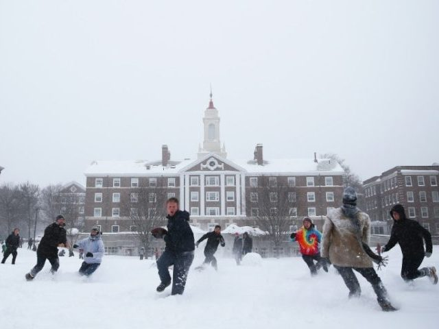 Students play football after a snowstorm on the campus of Harvard University in January 2015