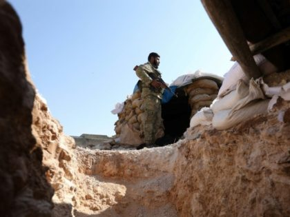 A Syrian rebel fighter from the National Liberation Front stands guard on August 31, 2018 over a trench as rebels prepare defensive positions in anticipation of an expected government assault on Idlib